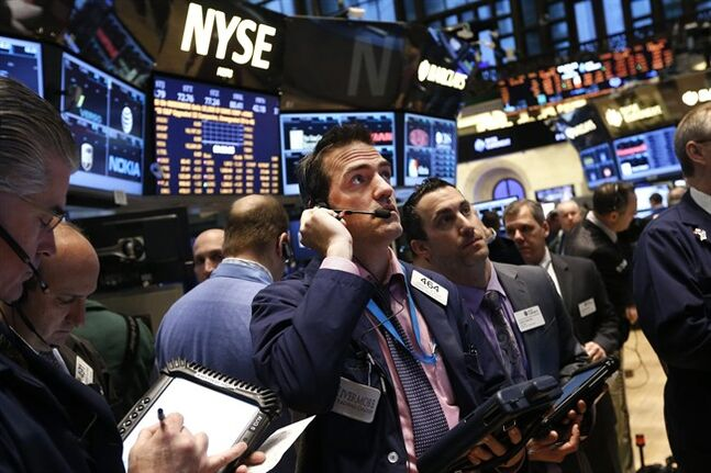 Trader Gregory Rowe, center, works on the floor of the New York Stock Exchange Friday, Jan. 24, 2014. (AP Photo/Jason DeCrow)