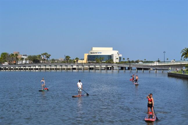 This March 22, 2011 photo provided by Three Brothers Boards shows Tour Guide Alex Page and tour customers across the street from the shop on a lesson/eco-tour on the Halifax River, Daytona Beach, Fla. A sort of combination between surfing and kayaking, standup paddling has exploded in popularity the past few years. It's relatively easy and can be done just about anywhere there's water. (AP Photo/Three Brothers Boards, Austin Marvin)