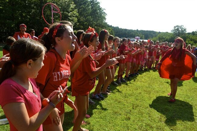 This August 2012 photo shows girls at Camp Hayward in Sandwich, Mass., on Cape Cod, during color wars. The photo was put up on the camp's website for parents to see. Many sleep-away camps now post photos daily so parents can see what their children are doing. (AP Photo/Camp Hayward)