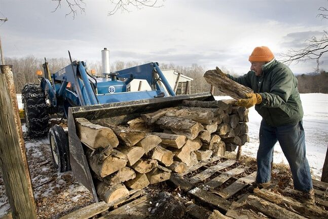 Devillo Peck works to load firewood in the back of his tractor at his home in Milford, N.Y., on Monday. Peck was gathering wood to prepare for the possibility of a snowstorm this week. (AP Photo/The Daily Star, Benjamin Patton)