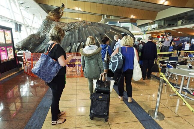 Passengers make their way around a giant eagle sculpture promoting