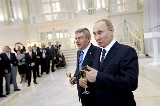 Russian President Vladimir Putin, right, and International Olympic Committee President Thomas Bach greet IOC members at a welcoming event ahead of the 2014 Winter Olympics at the Rus Hotel, Tuesday, Feb. 4, 2014, in Sochi, Russia. (AP Photo/David Goldman, Pool)