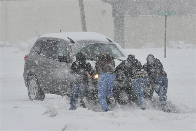 Good Samaritans help push a stranded motorist stuck in deep snow on Stefko Boulevard Thursday, Feb. 13, 2014 in Bethlehem, Pa. A wide swath of Pennsylvania awoke Thursday to a fresh coating of snow and a forecast for much more to come over the course of the day. (AP Photo/Chris Post)