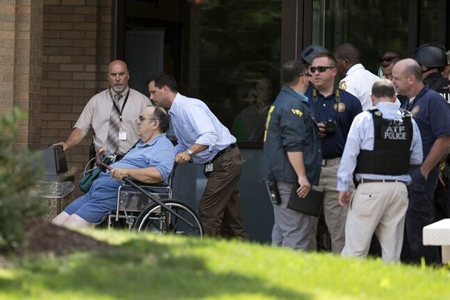 A patient is evacuated from the scene of a shooting at the Mercy Fitzgerald Hospital in Darby, Pa. on Thursday, July 24, 2014. A prosecutor said a gunman opened fire inside the psychiatric unit leaving one hospital employee dead and a second injured before being critically wounded himself. (AP Photo)