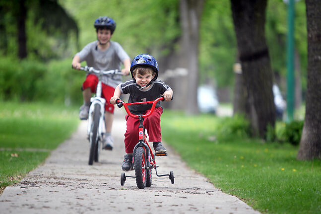 Three-year-old Yannick Sinclair races ahead of his brother Mehru, 9, along their sidewalk in the River Heights district of Winnipeg. Sporting bike helmets, these two are already getting a primer on obeying the law and cycling safety.