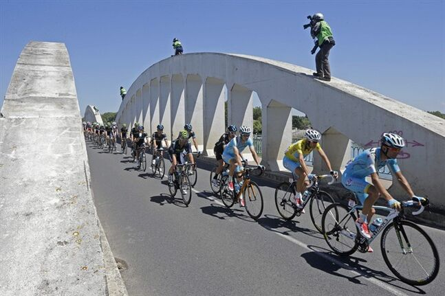 Photographers take pictures of the pack with Italy's Vincenzo Nibali, wearing the overall leader's yellow jersey, as it passes over a bridge during the twelfth stage of the Tour de France cycling race over 185.5 kilometers (115.3 miles) with start in Bourg-en-Bresse and finish in Saint-Etienne, France, Thursday, July 17, 2014. (AP Photo/Laurent Cipriani)