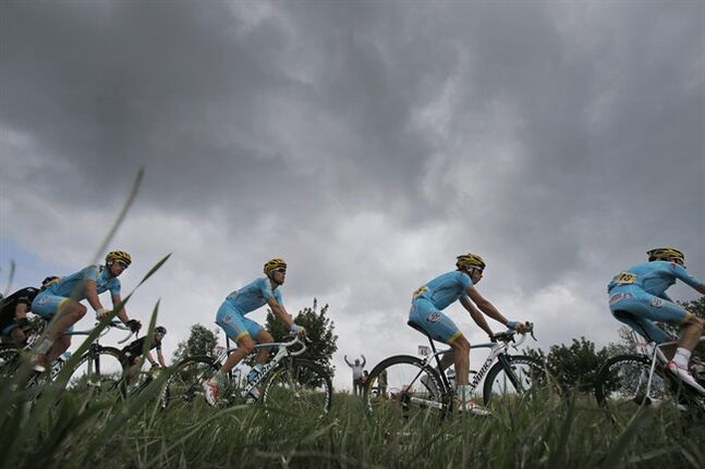 Team Astana with Kazakhstan's Dmitriy Gruzdev, Ukraine's Andriy Grivko, Kazakhstan's Maxim Iglinskiy, and Italy's Alessandro Vanotti, from left to right, lead the pack as it rides under menacing skies during the eighth stage of the Tour de France cycling race over 161 kilometers (100 miles) with start in Tomblaine and finish in Gerardmer, France, Saturday, July 12, 2014. (AP Photo/Christophe Ena)