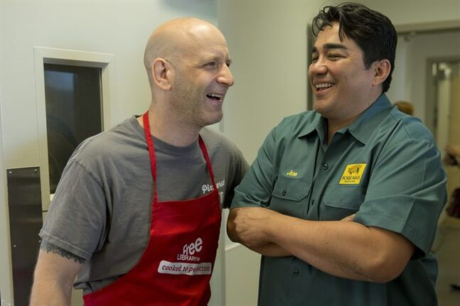 Chefs Marc Vetri, left, and Jose Garces meet at the Free Library of Philadelphia's Culinary Literacy Center, Monday, June 2, 2014, in Philadelphia. The newly opened a multimillion-dollar, state-of-the-art demonstration kitchen is an unusual culinary literacy program that aims to use cooking classes, renowned local chefs and specialized curricula as a way to improve literacy rates and nutrition habits in a city badly in need of both. (AP Photo/Matt Rourke)