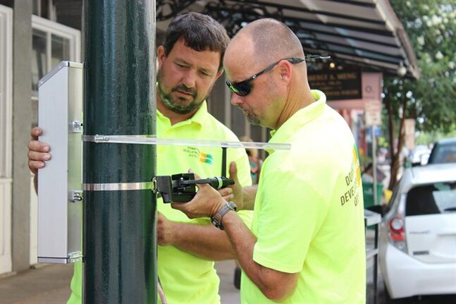 Dale Alvin, right, tightens the strap holding a cigarette butt recycling container to a lamp post in New Orleans' Warehouse District on Monday, July 21, 2014, while Jerry Howell holds it upright. The city's Downtown Development District plans to install about 50 of the receptacles around New Orleans in what manufacturer TerraCycle Inc. says is the first citywide cigarette butt recycling program in the United States. TerraCycle will pay $4 per pound for the cigarette waste, which it turns into shipping pallets. (AP Photo/Janet McConnaughey)