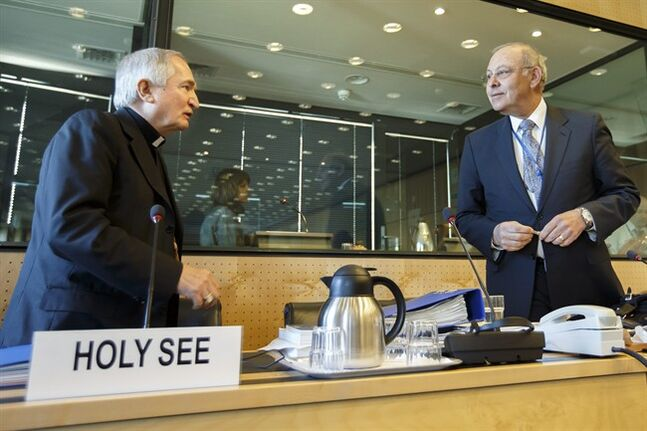 Archbishop Silvano M. Tomasi, left, Apostolic Nuncio, Permanent Observer of the Holy See (Vatican) to the Office of the United Nations in Geneva, speaks with Claudio Grossmann, right, Chairperson of UN Committee against Torture, prior the UN torture committee hearing on the Vatican, at the headquarters of the office of the High Commissioner for Human Rights (OHCHR) in the Palais Wilson, in Geneva, Switzerland, Monday, May 5, 2014. The UN Committee Against Torture hears the Holy See for the first time to consider whether the church's handling of child sexual abuse complaints has violated its obligations against subjecting minors to torture and to hear the Vatican on its efforts to stamp out child sex abuse by priests. (AP Photo/Keystone, Salvatore Di Nolfi)