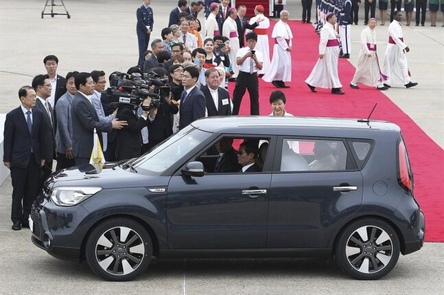 Pope Francis gets in a car as South Korean President Park Geun-hye, center, smiles upon his arrival at Seoul Air Base in Seongnam, South Korea, Thursday, Aug. 14, 2014. Pope Francis arrived for a five-day visit to South Korea to participate in a Catholic youth festival and to preside over a beatification ceremony for 124 Korean martyrs. (AP Photo/Ahn Young-joon. Pool)