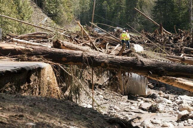Ministry of Transportation workers examine a large pile of debris of trees have taken out the bridge and road on Mable Lake Road along with power lines some 25 kilometres east of Enderby, B.C. on Friday, May 2, 2104. Some localized flooding is causing problems in the North Okanagan region. Vernon Search and Rescue teams have been scrambled due to concerns some residents may have been cut off by the high water. THE CANADIAN PRESS/Jeff Bassett