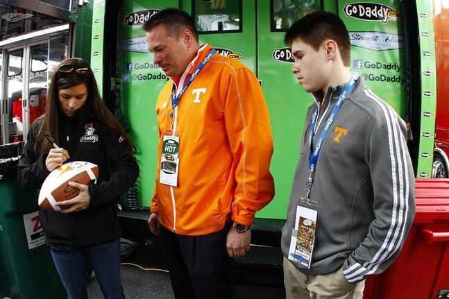 NASCAR Sprint Cup Series driver Danica Patrick, left, signs a football for Tennessee head football coach Butch Jones and his son Alex Jones before the Food City 500 auto race, Sunday, March 17, 2013, in Bristol, Tenn. (AP Photo/Wade Payne)