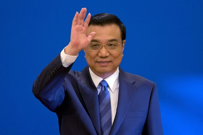 FILE - In this March 13, 2014 file photo, Chinese Premier Li Keqiang waves as he arrives for a press conference after the closing ceremony of the National People's Congress held in Beijing's Great Hall of the People, China. Li set off for a four-country tour of Africa on Sunday, May 4, 2014, acknowledging