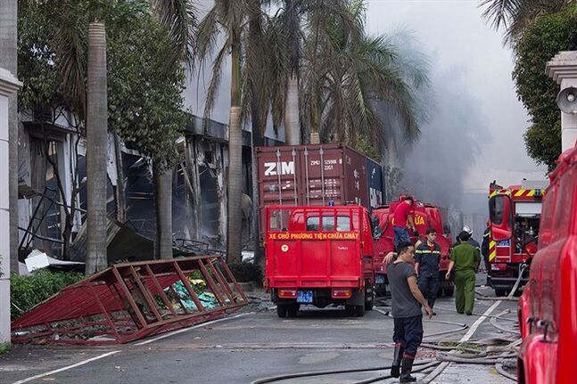 Firefighters stand across from the main entrance of Tan Than Industries as the Taiwanese bicycle factory burns, in Di An Town, Binh Duong province, Vietnam, Wednesday, May 14, 2014. Mobs burned and looted scores of foreign-owned factories in Vietnam following a large protest by workers against China's recent placement of an oil rig in disputed Southeast Asian waters, officials said Wednesday. (AP Photo/Jeff Nesmith)