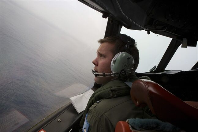 FILE - In this March 24, 2014 file photo, co-pilot, flying officer Marc Smith turns his Royal Australian Air Force AP-3C Orion aircraft at low level in bad weather whilst searching for missing Malaysia Airlines Flight 370 over the Indian Ocean. The Australian government plans to spend 90 million Australian dollars ($84 million) on the search for the missing Malaysian plane. Australia is leading the search for the missing plane, which is thought to have disappeared in the Indian Ocean with 239 people aboard on March 8. Budget documents released Tuesday, May 13, 2014 showed that the government has budgeted AU$90 million for the search in the current fiscal year through June and next fiscal year. (AP Photo/Richard Wainwright, Pool, File)