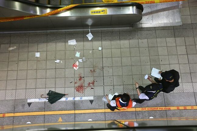 Police investigate the scene of a knife attack on a subway platform, in Taipei, Taiwan, Wednesday, May 21, 2014. AA drunken university student wielding a knife attacked riders aboard a subway train in Taiwan's capital on Wednesday, killing three people and injuring nearly two dozen others, police and local media said. (AP Photo)
