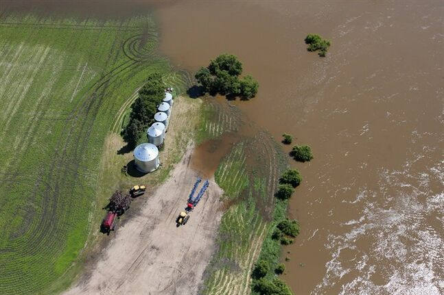 The swollen Assiniboine River covers farmland east of Brandon, Man. as seen from the air on Sunday, July 6, 2014. THE CANADIAN PRESS/Tim Smith