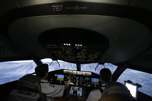 In this photo made Friday, May 9, 2014, American Airlines pilots Bill Elder, left, and Jim Dees work inside a Boeing 787 flight simulator in Fort Worth, Texas. In the next few months, dozens of American Airlines pilots will sit in the same simulator and learn the nuances of the controls before they can fly the real plane, which the airline will begin using for passenger flights early next year. (AP Photo/LM Otero)