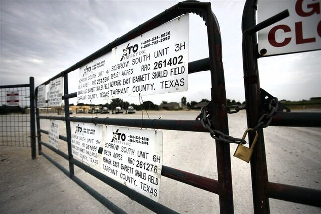Signs on a locked gate show the number of operating wells at an XTO Energy Inc site, Saturday, June 21, 2014, in Azle, Texas. Earthquakes used to be unheard of on the vast stretches of prairie that unroll across Texas and Oklahoma. But in recent years, temblors have become commonplace. Oklahoma recorded 145 of them just between January and the start of May. (AP Photo/Tony Gutierrez)