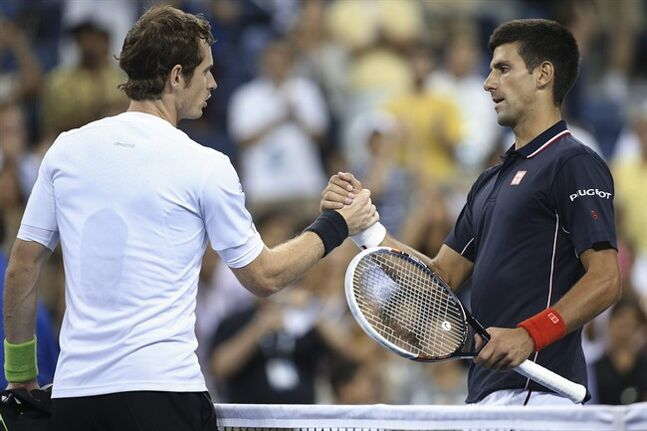 Novak Djokovic, right, of Serbia, clasps hands with Andy Murray, of Britain, at the net after a quarterfinal of the U.S. Open tennis tournament, early Thursday, Sept. 4, 2014, in New York. Djokovic won 7-6 (1), 6-7 (1), 6-2, 6-4. (AP Photo/John Minchillo)