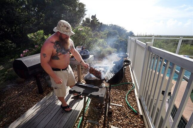 Shawn Jewell grills spare ribs outside the the home where he is vacationing with friends in Avon, N.C., on Hatteras Island as Tropical Storm Arthur comes up the up the Atlantic coast on Wednesday, July 2, 2014. He and his friends had begun packing up their belongings and would be ready to leave if an evacuation is called for. (AP Photo/The Virginian-Pilot, Steve Earley) MAGS OUT