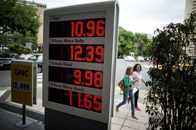 Two women walk by a digital price board displaying fuel prices at a Shell gas station in Buenos Aires, Argentina, Monday, Feb. 3, 2014. Shell increased prices an average of 12 percent. (AP Photo/Victor R. Caivano)