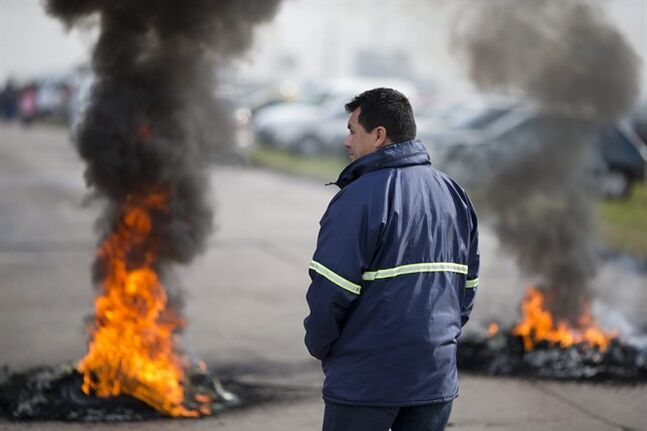 A worker stands next to burning tires outside the entrance of RR Donnelley printing plant in the outskirts of Buenos Aires, Argentina, Monday, Aug. 11, 2014. RR Donnelley, a Fortune 500 company from Chicago, closed its plant in Argentina without warning catching its 400 workers by surprise when they showed up for work Monday morning. The company posted a letter outside it's entrance announcing its closing due to