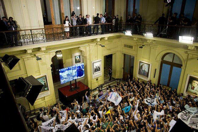 Argentine President Cristina Fernandez, left, speaks to supporters during an event at the Casa Rosada government palace in Buenos Aires, Argentina, Wednesday, Feb. 12, 2014. (AP Photo/Victor R. Caivano)