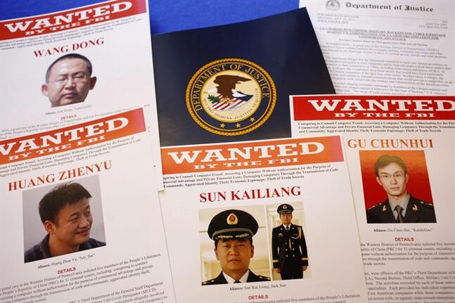 FILE - This May 19, 2014 file photo shows press material displayed at the Justice Department in Washington before a press conference by U.S. Attorney General Eric Holder to announce charges of economic espionage and trade secret theft against five Chinese military officers, all hackers in an international cyber-espionage case. In the two weeks since the Obama administration accused them of hacking into American companies to steal trade secrets, the Chinese officers have yet to be placed on Interpol's public listing of international fugitives, and there is no evidence that China would even entertain a formal request by the U.S. to extradite them. (AP Photo/Charles Dharapak, File)
