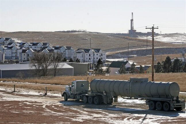 FILE - In this Feb. 26, 2014, file photo, an oil truck sits in a dirt lot near a new housing development in Watford City, N.D. The United States is still growing older, but the trend is reversing in the Great Plains, thanks to a liberal application of oil. (AP Photo/Martha Irvine)