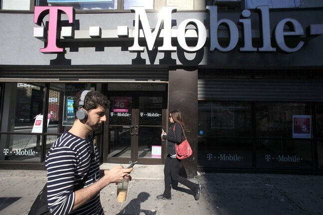 FILE - This Sept. 12, 2012 file photo shows a man using a cellphone as he passes a T-Mobile store in New York. T-Mobile USA knowingly made hundreds of millions off its customers in bogus charges, a federal regulator alleged Tuesday in a complaint that is likely to damage the reputation of a household name in wireless communications. In its complaint filed in federal court, the Federal Trade Commission claimed that T-Mobile billed consumers for subscriptions to premium text services such as $10-per-month horoscopes that were never authorized by the account holder. The FTC alleges that T-Mobile collected as much as 40 percent of the charges, even after being alerted by other customers that the subscriptions were scams. (AP Photo/Mark Lennihan, File)