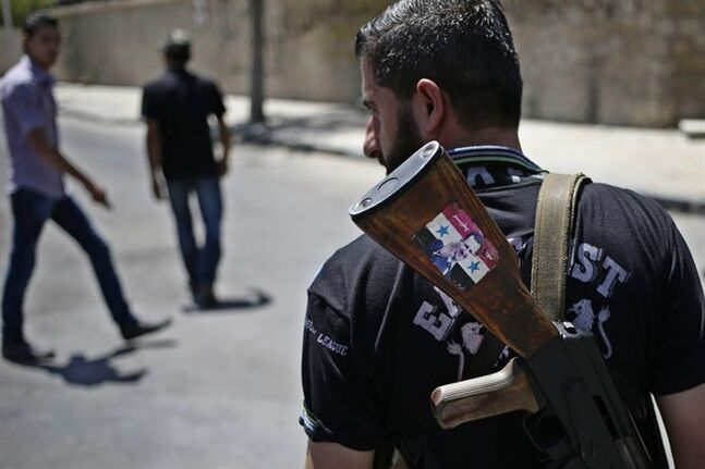 FILE - This Aug. 21, 2013 file photo shows a Syrian military soldier holding his AK-47 with a sticker of Syrian President Bashar Assad and Arabic that reads,
