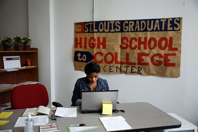 This photo taken June 10, 2014, shows intern Daisha Tanking working at the St. Louis High School to College Center in St. Louis. A drop-in counseling center akin to a pop-up retail store, the center helps low-income students make the transition to college by negotiating financial aid agreements, housing contracts and the other myriad details of college enrollment. (AP Photo/Jeff Roberson)