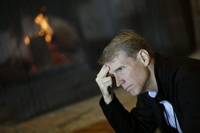 Timothy Adams, president and chief executive officer of the Institute of International Finance, sits by a fire during a break at the Jackson Hole Economic Policy Symposium at the Jackson Lake Lodge in Grand Teton National Park near Jackson, Wyo. Saturday, Aug. 23, 2014. (AP Photo/John Locher)