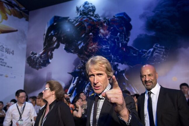 In this Monday June 23, 2014 photo, director Michael Bay, center, gestures to fans as he attends the premiere of movie