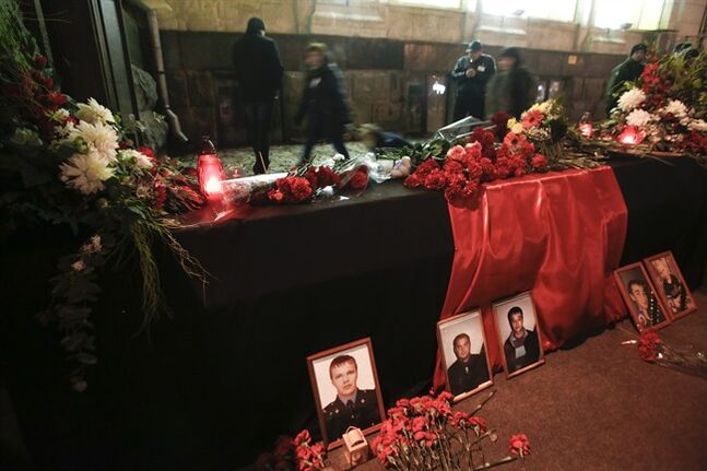 Flowers and portraits of victims are placed at an entrance to Volgograd main railway station in Volgograd, Russia, Monday, Dec. 30, 2013. Russian authorities ordered police to beef up security at train stations and other facilities across the country after a suicide bomber killed 14 people on a bus Monday in the southern city of Volgograd.It was the second deadly attack in two days on the city that lies just 400 miles (650 kilometers) from the site of the 2014 Winter Olympics. (AP Photo/Denis Tyrin)