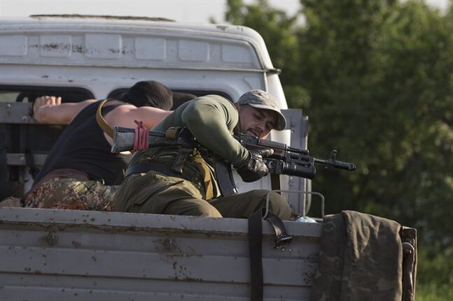 Pro-Russian men hold their weapons atop a vehicle as they arrive to support their comrades at a checkpoint outside Slovyansk, eastern Ukraine, Thursday, May 15, 2014. On Thursday, Ukraine's acting president, Oleksandr Turchynov, claimed the Ukrainian army destroyed an insurgent base in the city of Slovyansk and another one in nearby Kramatorsk, about 150 kilometers (95 miles) west of the Russian border. (AP Photo/Alexander Zemlianichenko)