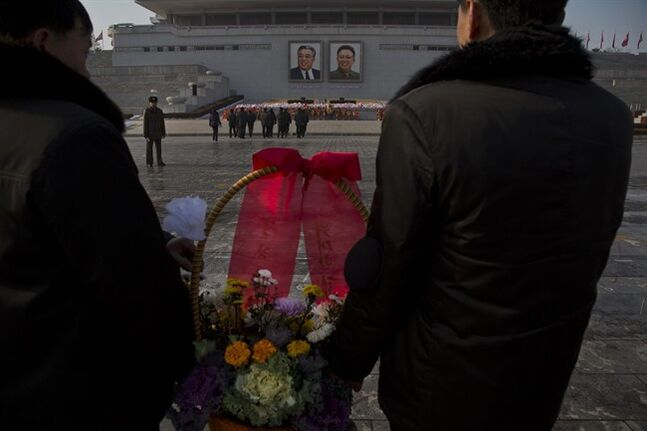 North Koreans lay flowers beneath portraits of the late leaders Kim Jong Il and Kim Il Sung in Pyongyang on Tuesday, Dec. 17, 2013. Across the capital city, North Koreans observed the second anniversary of the death of Kim Jong Il. (AP Photo/David Guttenfelder)
