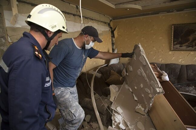 Rescue workers examine the damage in a house after shelling in Maryinka village outside the city of Donetsk, eastern Ukraine Saturday, July 12, 2014. (AP Photo/Dmitry Lovetsky)