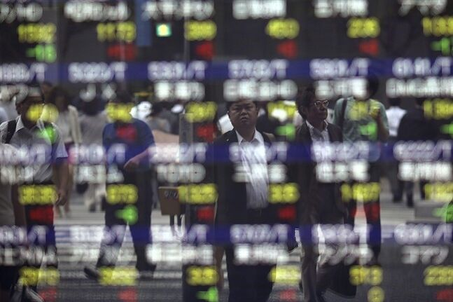 Pedestrians are reflected on an electronic stock board of a securities firm in Tokyo, Thursday, July 17, 2014. Asia's major stock markets mostly posted modest gains Thursday after positive U.S. corporate and economic news underpinned confidence. (AP Photo/Eugene Hoshiko)