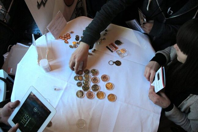 Attendees of the Inside Bitcoins conference in Berlin examine Bitcoin buttons on Wednesday, Feb. 12, 2014. The conference brought together entrepreneurs and enthusiasts of the virtual currency to discuss business opportunities and recent developments. (AP Photo/Frank Jordans)