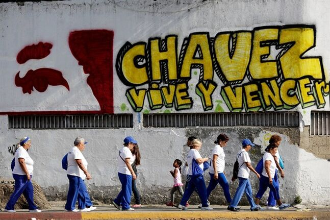 Pedestrians walks past graffiti that reads in Spanish;