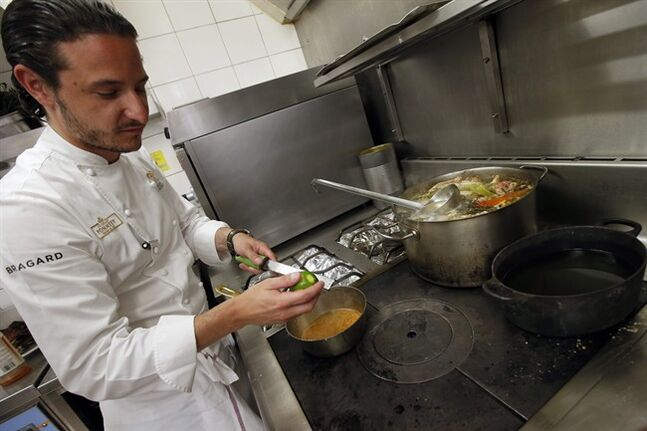 French Chef Pierre Meneau works in the kitchen of his restaurant Crom'Exquis in Paris, France, Wednesday, July 16, 2014. Restaurant-goers in France will start seeing a funny little symbol on their menus this week: a skillet with a house on top, indicating your menu choice is made in-house, as part of a new law meant to battle against the surprising amount of factory-made, pre-packaged food in French restaurants. (AP Photo/Francois Mori )