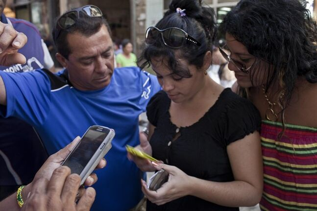 In this May 9, 2014 photo, people try to connect to the Etecsa server as they wait with other customers outside the offices of the state telecom monopoly Etecsa in Havana, Cuba. Cuba's government blames their technological problems on a U.S. embargo that prevents most American businesses from selling products to the Caribbean country. Critics of the government say it deliberately strangles the Internet to halt the spread of dissent. (AP Photo/Franklin Reyes)