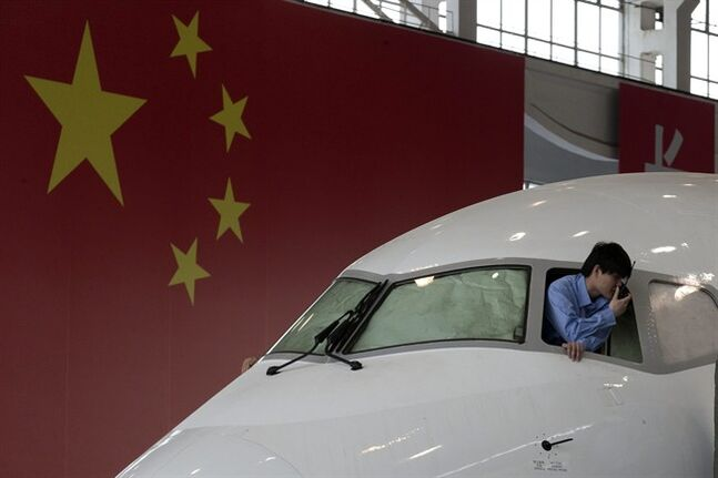 A worker peers out from the cockpit of a almost completed COMAC ARJ21-700 passenger jet at a final assembly and manufacturing center in Shanghai , China, Wednesday, May 21, 2014. China's state-owned plane maker Comac said Wednesday they were ready to deliver their first regional airliner and were on track to deliver their greater distance-flying narrow-body airplane to customers in 2018. (AP Photo/Ng Han Guan, Pool)