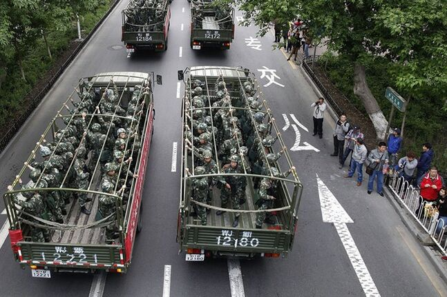In this Friday, May 23, 2014 photo, armed paramilitary policemen ride on military trucks during a show off force on the streets of Urumqi in northwest China's Xinjiang province. Police in China's restive northwest foiled a terror plot by detaining five suspects and seizing 1.8 tons of bomb-making materials, the regional government said Tuesday, May 27, 2014, five days after a market bombing in the region killed dozens of people. (AP Photo) CHINA OUT