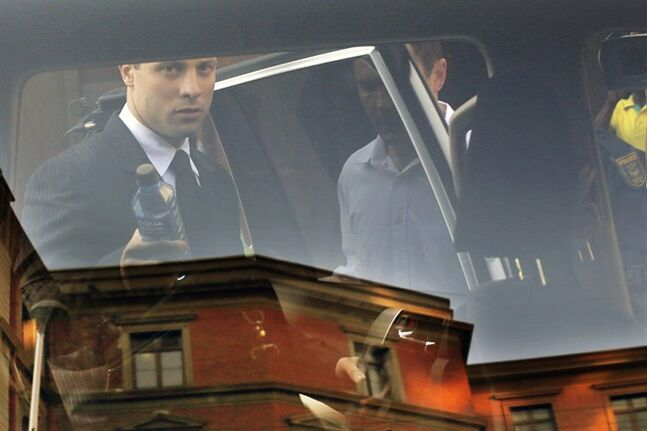 Seen through a car window, Oscar Pistorius leaves the court, in Pretoria, South Africa, Wednesday, July 2, 2014. Pistorius is severely traumatized after killing girlfriend Reeva Steenkamp last year and will become an increasing suicide risk unless he continues to get mental health care, the judge overseeing his murder trial heard on Wednesday. Defense lawyer Barry Roux read excerpts from a psychologist's report that said the double-amputee runner is suffering depression and post-traumatic stress disorder and