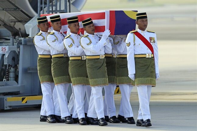 Malaysian Army soldiers carry a coffin containing the body of Mohd Ghafar Abu Bakar, a Malaysia Airlines in-flight supervisor who was among the victims onboard Flight MH17, upon arrival at Kuala Lumpur International Airport in Sepang, Malaysia, Sunday, Aug. 24, 2014. (AP Photo/Lai Seng Sin)