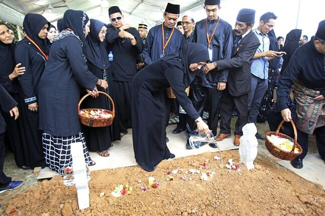Sharom Ibrahim, center, mother of Nur Shazana, a Malaysia Airlines crew member who was among the victims onboard Flight MH17, pours water on her grave during a burial ceremony at Taman Selatan Muslim cemetery in Putrajaya, Malaysia, Friday, Aug. 22, 2014. Carried by soldiers and draped in the national flag, coffins carrying bodies and ashes of 20 Malaysian victims of Flight MH17 returned home Friday to the country still searching for those onboard another doomed jet and a government battling the political fallout of the twin tragedies. (AP Photo/Lai Seng Sin)